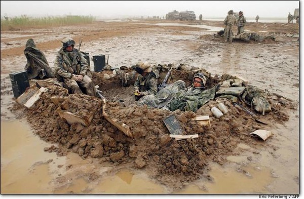 Soldiers laying in mud, Kuwait, 2003