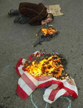 Smelly hippie lights cig on burning American flag