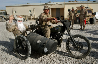 Capt. Clace Perzel rides a military motorcycle side-car dressed as Santa Claus, Ghazni province, Afghanistan